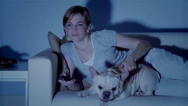 ms, young woman with dog lying on sofa, watching tv - haustierbesitzer stock-videos und b-roll-filmmaterial