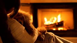 Young woman with dog sitting by the fireplace.
