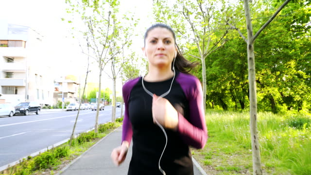young woman with earphones running on the sidewalk. - attitude stock videos & royalty-free footage
