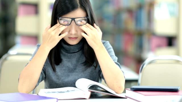 stockvideo's en b-roll-footage met jonge vrouw met ogen pijn aanraken van haar ogen - bril brillen en lenzen