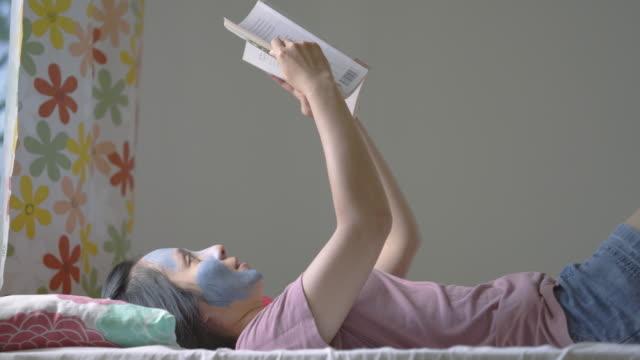 vídeos de stock, filmes e b-roll de jovem com máscara facial deitada de costas curtindo livro - spa