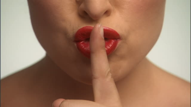 SLO MO, ECU, Young woman with finger on lips