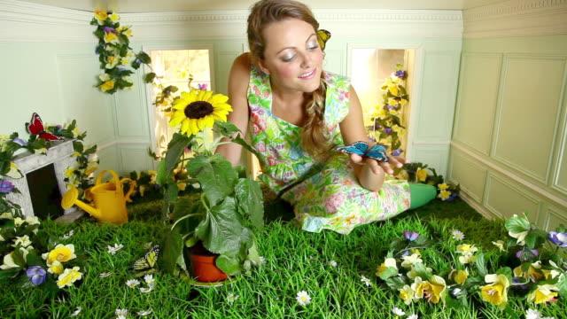 young woman with garden in small room - fångad bildbanksvideor och videomaterial från bakom kulisserna