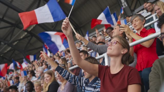 young woman with glasses waving the french flag sitting on the stadium tribune - french flag stock videos & royalty-free footage