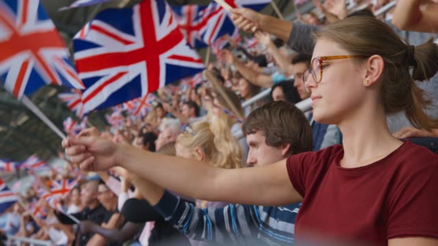 Young woman with glasses waving the Union Flag on the stadium tribune