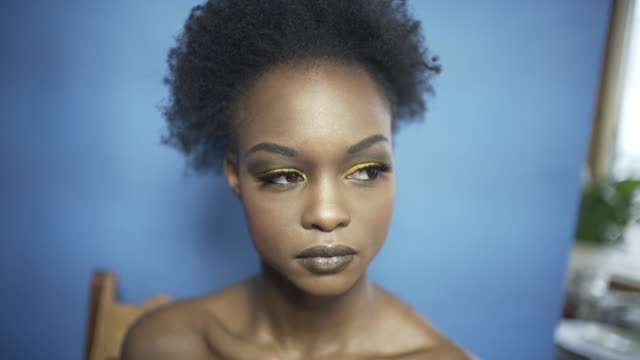a young woman with gold eye shadow and long false eye lashes. - natural black hair stock videos & royalty-free footage