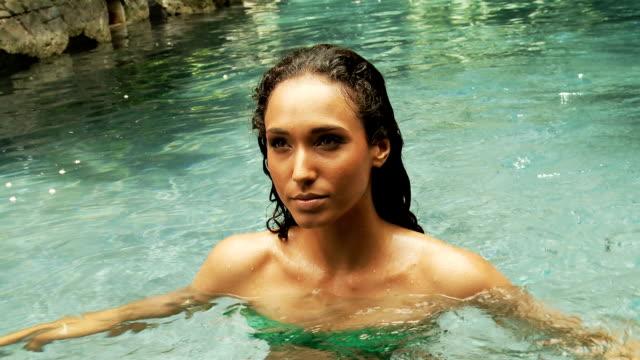 Young woman with green bikini in a pool