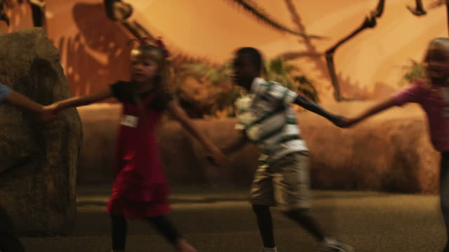 vidéos et rushes de ms young woman with group of children (4-5, 6-7, 8-9) walking in natural history museum, holding hands, lehi, utah, usa - lehi
