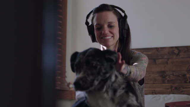 stockvideo's en b-roll-footage met ms slo mo. young woman with headphones calls dog up on bed and pets her sweetly. - alleen één mid volwassen vrouw