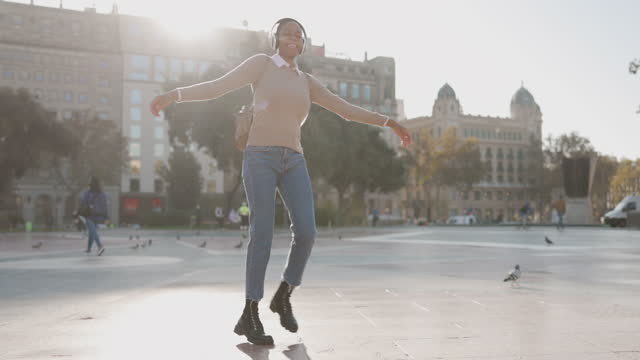 young woman with headphones dancing at city - escapism stock videos & royalty-free footage