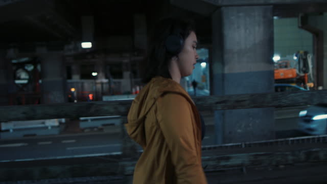 vídeos y material grabado en eventos de stock de young woman with headphones walking at night in tokyo, japan - música