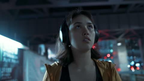 vídeos y material grabado en eventos de stock de young woman with headphones walking, looking up at night in tokyo, japan - resistencia