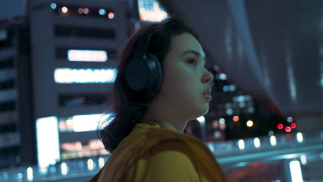 young woman with headphones walking under bridge at night in tokyo, japan - electrical equipment stock videos & royalty-free footage