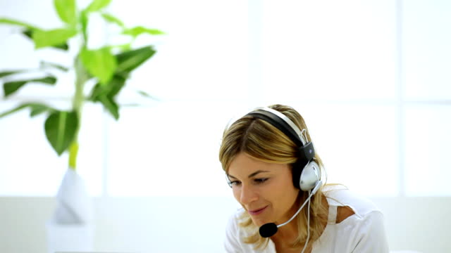 young woman with headset and laptop. - headset stock videos & royalty-free footage