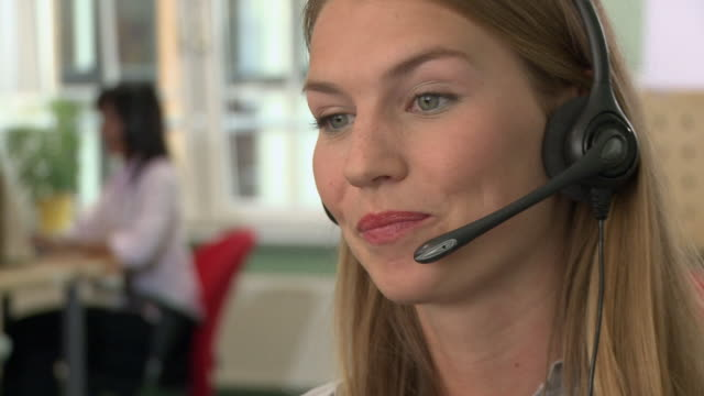 cu, selective focus, young woman with headset in call center - call center stock videos & royalty-free footage