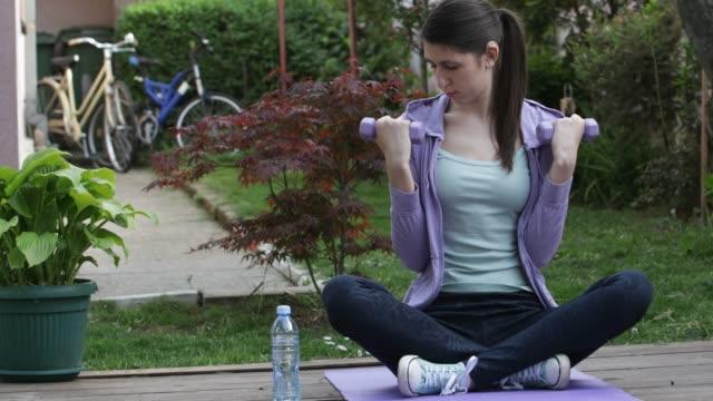 vídeos de stock, filmes e b-roll de mulher nova com o aparelho auditivo que exercita no jardim formal - coque cabelo para cima