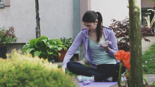 vídeos y material grabado en eventos de stock de jovencita con audífono haciendo ejercicio en jardín formal - sordera