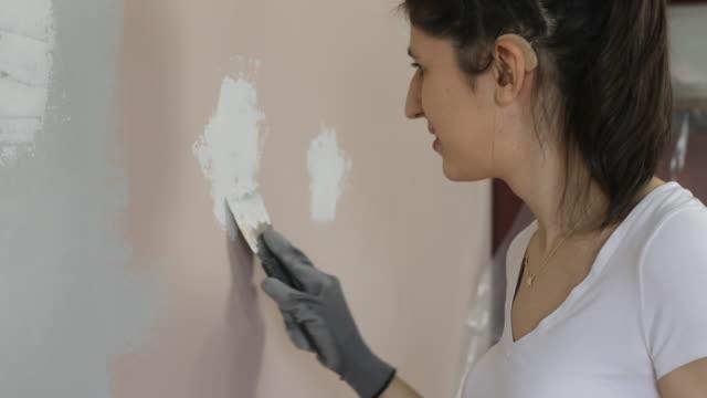 vídeos y material grabado en eventos de stock de mujer joven con audífonos pintando paredes - sordera
