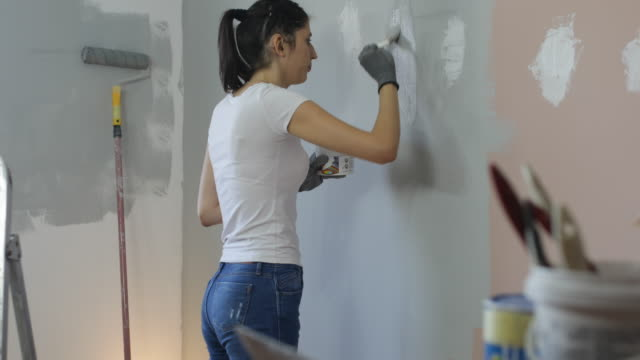 young woman with hearing aid painting walls - hearing loss stock videos & royalty-free footage