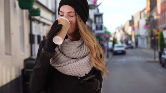 Young woman with her coffee laughing at boyfriend's text