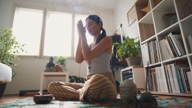 junge frau mit geschlossenen augen halten hände in namaste geste, während meditieren an - gebetsposition stock-videos und b-roll-filmmaterial