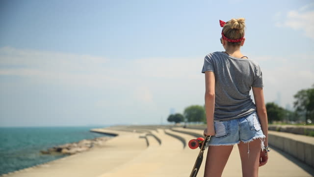 a young woman with her longboard skateboard. - shorts stock-videos und b-roll-filmmaterial