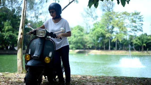 vídeos y material grabado en eventos de stock de mujer joven con su scooter. - examinar