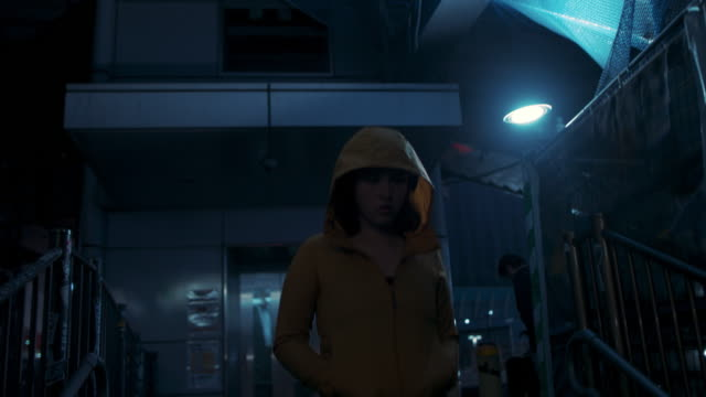 young woman with hooded jacket walking at night in tokyo, japan - generation z stock videos & royalty-free footage