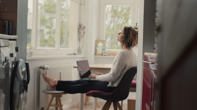 stockvideo's en b-roll-footage met young woman with laptop on knees, looking up, thinking at home in berlin - telewerk