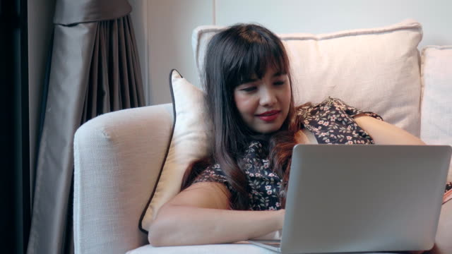 young woman with laptop working on sofa - only young women stock videos & royalty-free footage