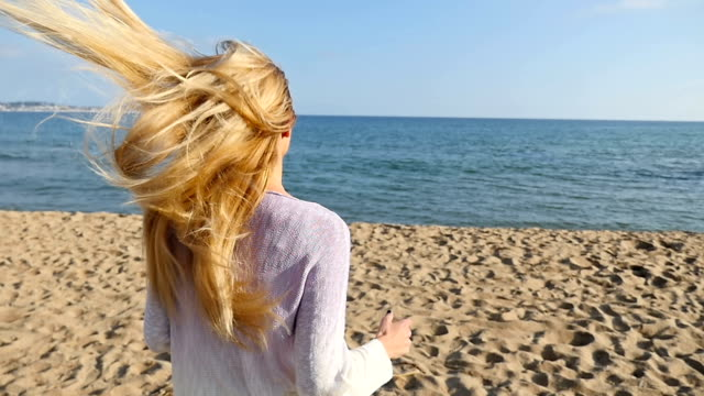 young woman with long hair running at the beach - long hair stock videos and b-roll footage