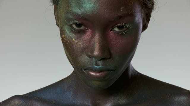 Young woman with metallic makeup on face