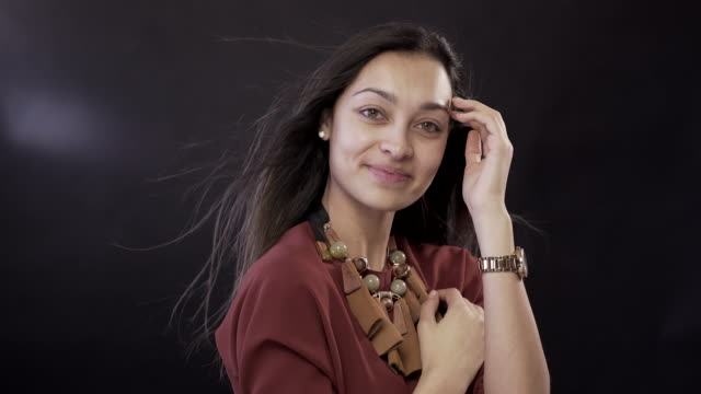 young woman with no make-up on a black background with wind in her hair - no make up stock videos & royalty-free footage