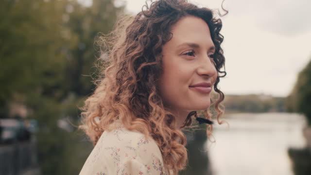 vídeos de stock, filmes e b-roll de young woman with nose piercing sitting by spree river in berlin - cabelo encaracolado