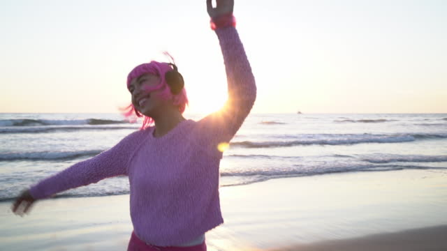 SM Young woman with pink hair dancing on the beach at sunset