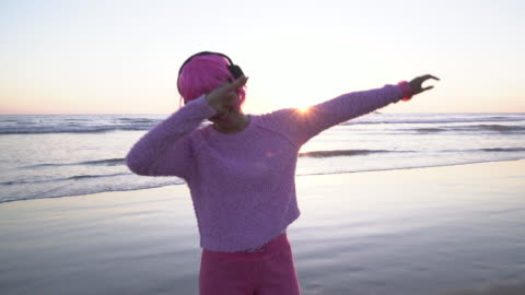 vidéos et rushes de ms young woman with pink hair dancing on the beach - casque