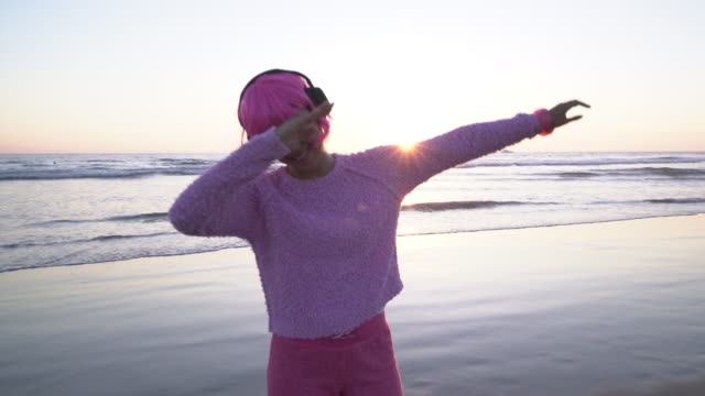stockvideo's en b-roll-footage met ms young woman with pink hair dancing on the beach - hoofdtelefoon