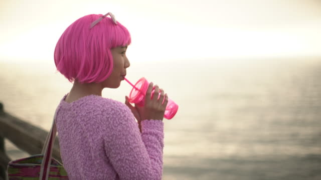 vídeos de stock, filmes e b-roll de ms young woman with pink hair drinking out of a pink cup - na moda descrição