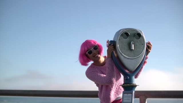 ms young woman with pink hair having fun on holiday - binoculars stock videos & royalty-free footage