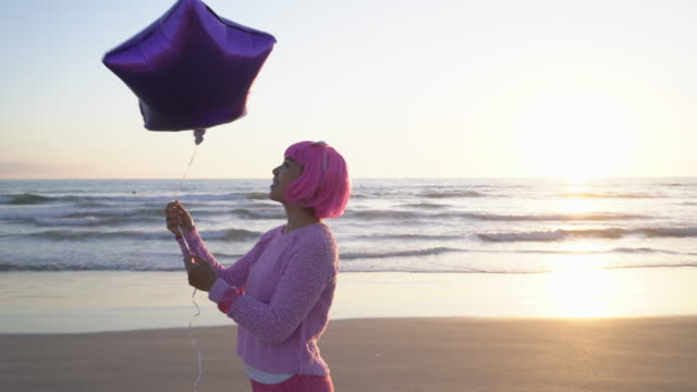 ms young woman with pink hair holding a balloon on the beach - funky stock videos & royalty-free footage
