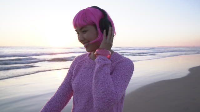 ms young woman with pink hair listening to music on the beach - pink hair stock videos & royalty-free footage