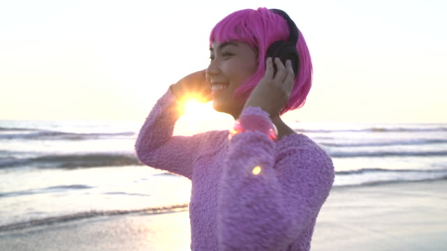 sm ms young woman with pink hair listening to music on the beach. - pink hair stock videos & royalty-free footage