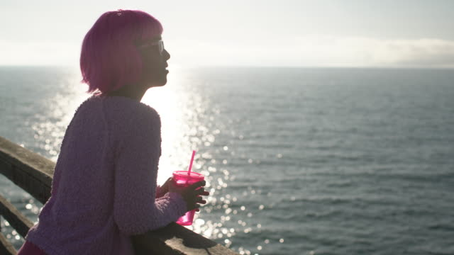 MS Young woman with pink hair looking at the ocean