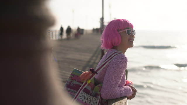 ms young woman with pink hair looking at the ocean - pink hair stock videos & royalty-free footage