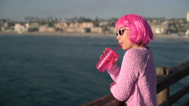 ms young woman with pink hair looking at the sea drinking - pink hair stock videos & royalty-free footage