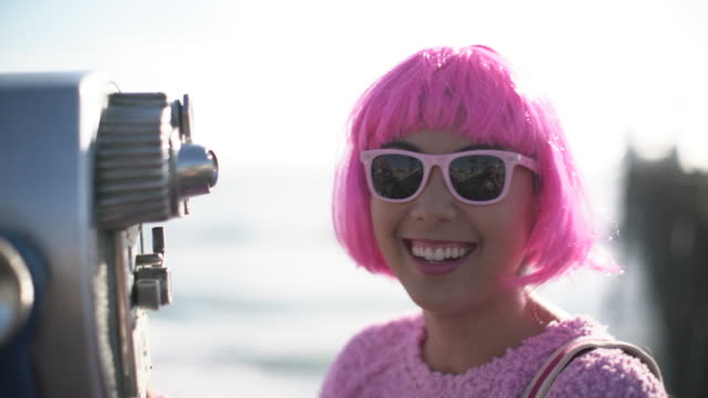 cu young woman with pink hair looking through binoculars - hot pink stock videos & royalty-free footage
