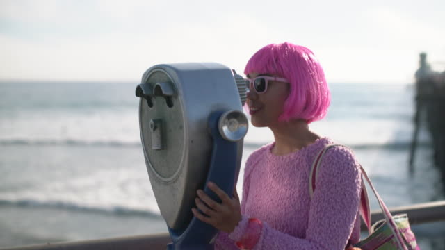 ms young woman with pink hair looking through giant binocular - pink hair stock videos & royalty-free footage