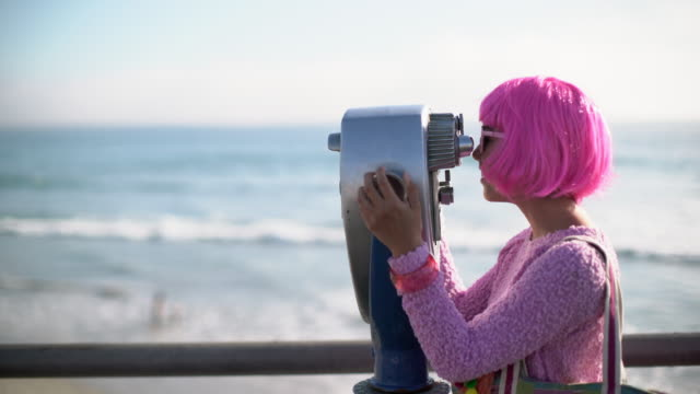 ms young woman with pink hair looking through giant binoculars - binoculars stock videos & royalty-free footage