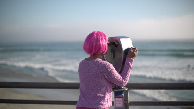 ms rv young woman with pink hair looking through telescope at the beach - pink hair stock videos & royalty-free footage