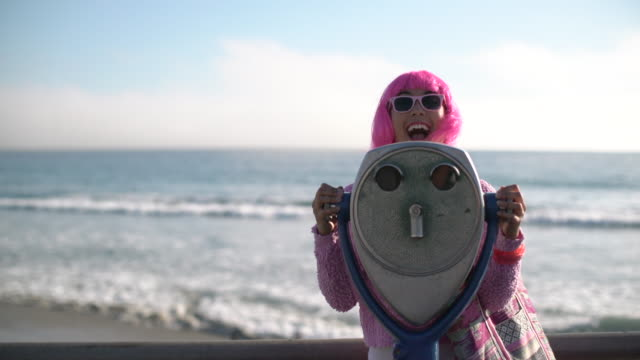 ms young woman with pink hair playing around with giant binoculars - binoculars stock videos & royalty-free footage